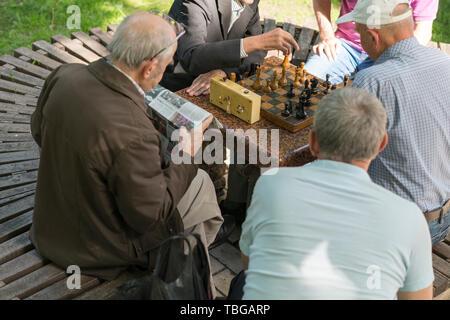 Attivi i pensionati, amici di vecchia data e tempo libero, seniors divertirsi e giocare a scacchi gioco al parco. Vita. Gli uomini anziani giocare a scacchi nel parco. Foto Stock