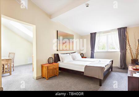 Interiore camera da letto in soppalco di lusso, soffitta, appartamento con finestre da tetto - Hotel camera - Concetto di vacanza sfondo Foto Stock