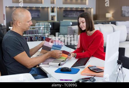 Consulente maschio aiutando giovane donna scelta di tessuti di tappezzeria nel negozio di arredamento. Focus sulla donna Foto Stock