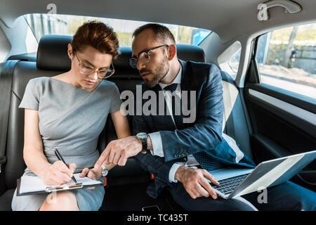 Bello imprenditore puntando con il dito in corrispondenza di appunti durante la seduta con il computer portatile nei pressi di donna in auto Foto Stock