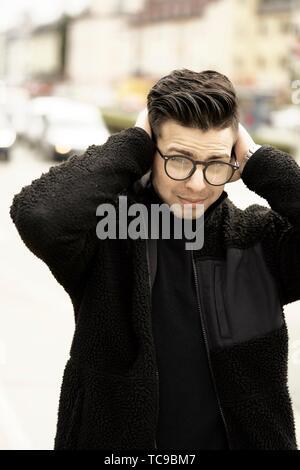 Giovane uomo preoccupato in città, toccando la testa, indossando occhiali, vestito nero, a Monaco di Baviera, Germania. Foto Stock