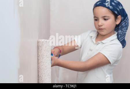 Bambina con rullo di vernice in mano. Bambini aiutando Casa concetto. Foto Stock