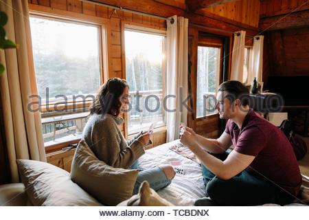 Giovane giocando a carte sul letto di cabina Foto Stock