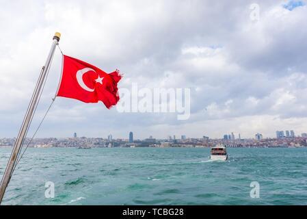 Vista del Bosforo ,costa e mare baia dal traghetto con bandiera turca agitando contro il cielo blu di Istanbul, Turchia. 03 gennaio 2018. Foto Stock