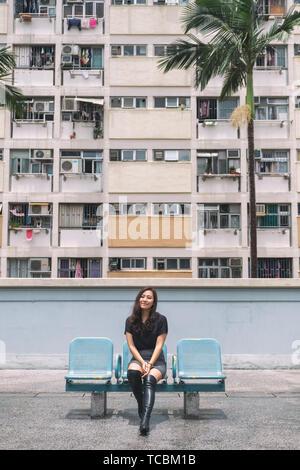 Immagine ritratto di una bella donna asiatica con lo stile vintage colori pastello edificio in Hong Kong Foto Stock