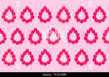 Donne medico periodi di sfondo. Red pillole in forma di gocce di sangue su un sfondo rosa. Vista dall'alto. Foto Stock