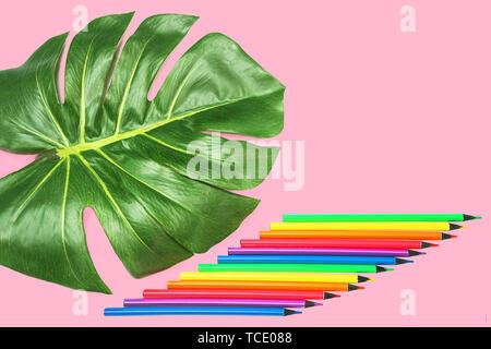 Torna a scuola con sfondo verde foglia di monstera, luci al neon colorate matite sul rosa pastello sullo sfondo.