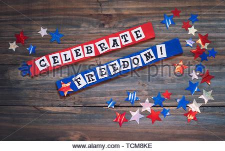 Quarto di luglio segno con parole che dire celebrare la libertà. È in rosso, bianco e blu con stelle luccicanti con riflessi di luce, tutti su rustiche dark wo Foto Stock