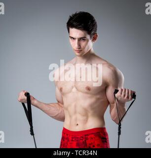 fbb2d6aec461 ... Ritratto in studio giovane uomo caucasico su sfondo grigio in posa. Tema  della pubertà,