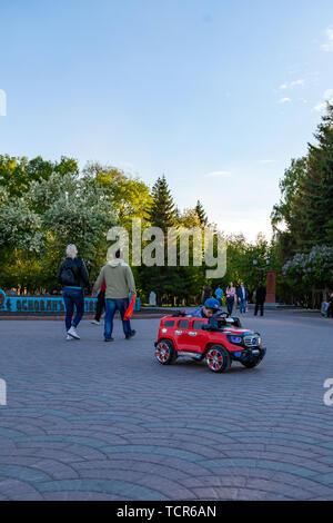 Novosibirsk, Russia - 05.28.2019: Un piccolo ragazzo corse in rosso di un auto elettrica mentre si cammina con i suoi genitori in un parco cittadino con verdi alberi, ridendo e Foto Stock
