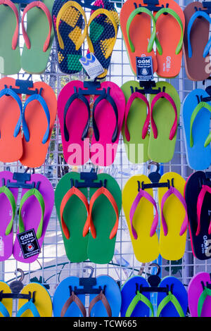 Una chiusura di un wall display colorato e flip flop per la vendita, colori includono, verde, rosso e giallo Foto Stock