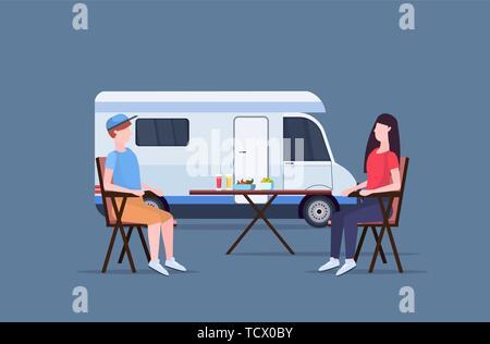 Coppia seduta al tavolo vicino camping famiglia camion con rimorchio caravan auto uomo donna spendingtime insieme la vacanza estiva concetto flat a piena lunghezza Foto Stock
