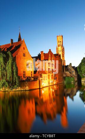 Famosa vista di Bruges turistico attrazione landmark - Rozenhoedkaai canal con la torre campanaria e le vecchie case lungo il canal grande e con albero nella notte. Belgio