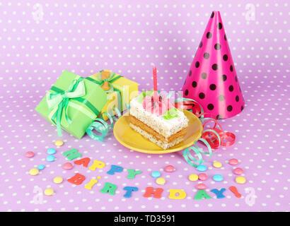 Colorate torta di compleanno con candela e doni su sfondo rosa Foto Stock