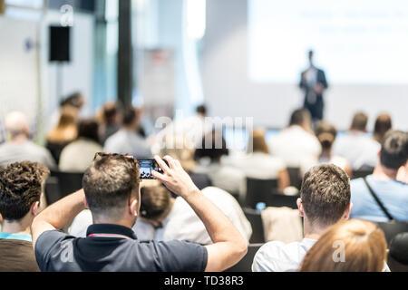 Maschio altoparlante aziendali fornendo un discorso alla conferenza di business event. Vista posteriore del partecipante non riconosciuto in udienza prendendo foto della presentazione. Foto Stock