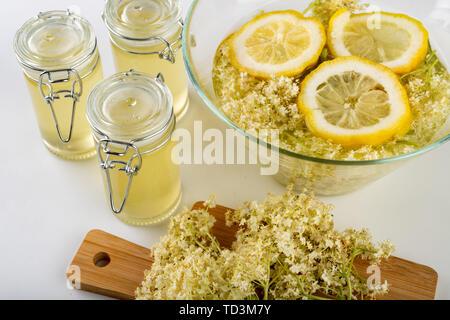 Succo di fiori di sambuco nero su un tavolo bianco. Terapeutici sciroppo freddo preparato per lo stoccaggio per l'inverno. Sfondo chiaro. Foto Stock