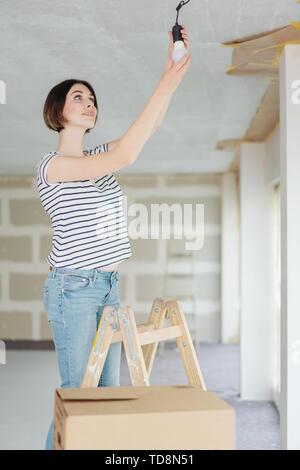 Giovani in piedi su una scala donna cambiare una lampadina in una stanza in fase di ristrutturazione