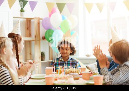Ritratto di sorridente ragazzo afro-americano che indossa la corona seduta a tavola mentre festeggia il compleanno con gli amici, spazio di copia Foto Stock