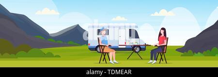Coppia seduta al tavolo vicino camping famiglia camion con rimorchio caravan auto uomo donna spendingtime insieme estate Concetto di vacanza bella natura paesaggio Foto Stock