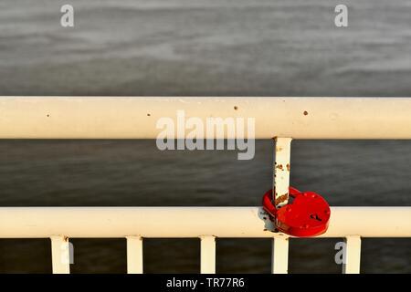 Il dipinto di bianco di ringhiera degli argini del fiume. Con un dispositivo di bloccaggio rosso montato su un tubo di metallo. Le linee di reticolo sullo sfondo dell'acqua. Su Su Foto Stock