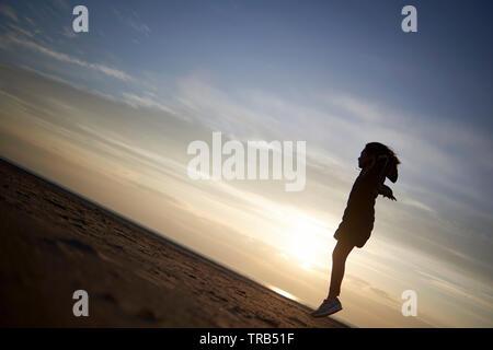 Silhouette di una giovane ragazza del salto in aria in alto in un arido paesaggio spiaggia rendendo il look come se lei è leggero e galleggiante in midair Foto Stock