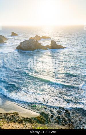 Il sole di setting crea ombre dietro pile di mare lungo una bellissima costa, Big Sur, California, Stati Uniti d'America. Foto Stock