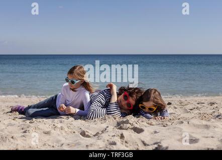 A piedi mamme con bambini sulla spiaggia. Sorelle di 8 e 7 anni) e il fratello più giovane (3 anni) stanno giocando a mare. Messa a fuoco selettiva. Foto Stock