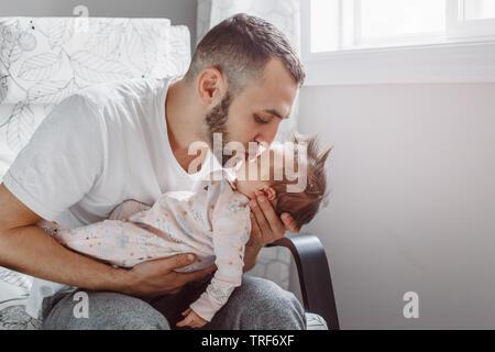 Padre caucasica seduto in poltrona con neonato ragazza. Genitore in possesso di baciare bambino figlia figlio nelle sue mani. Un autentico stile di vita documentario m
