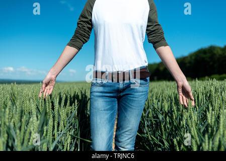 La donna in esecuzione le sue mani attraverso la maturazione del grano in un campo vicino. Foto Stock