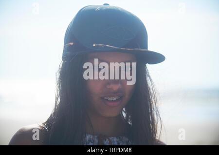 Ritratto di un giovane adolescente ragazza asiatica che indossa un nero cappello da baseball in spiaggia in una giornata di sole Foto Stock