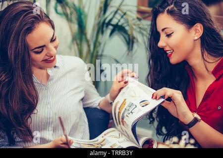 Happy amici di sesso femminile di parlare e di bere il caffè durante la lettura della rivista in un cafe Foto Stock