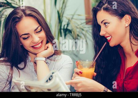 Happy amici di sesso femminile di parlare e di bere succo di frutta fresca durante la lettura della rivista in un cafe Foto Stock
