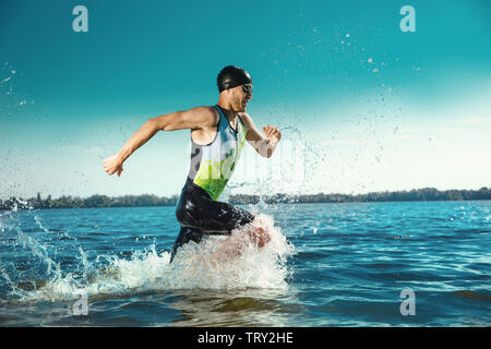 Professional triatleta nuotare nel fiume di acqua aperta. Uomo di indossare attrezzature di nuoto triathlon praticanti sulla spiaggia nel giorno d'estate. Concetto di stile di vita sano, sport, azione, movimento e movimento. Foto Stock