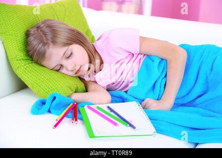 Bambina che dorme sul divano in camera Foto Stock