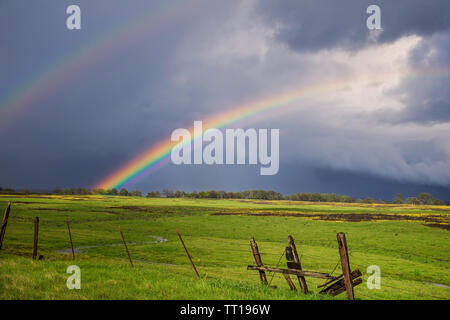Incredibile doppio arcobaleno su un prato tranquillo paesaggio delimitato da un vecchio rotto filo spinato. Foto Stock