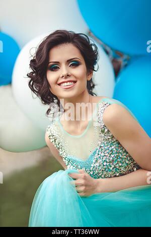 Ritratto di una bella ragazza laureata in un vestito blu con big blu e bianco palloncini. Una ragazza dolce con un bel sorriso. Foto Stock