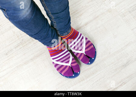 I piedi femminili in calze con rosa flip-flop, su sfondo a pavimento Foto Stock