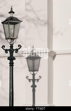 Classic street lampada e la sua ombra sul muro di una chiesa in una giornata di sole Foto Stock