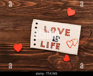Iscrizione amore è vita sul cartone ritagliata su sfondo di legno Foto Stock