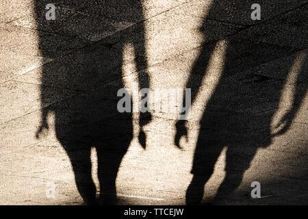 Le ombre sagome di giovane uomo e donna in piedi sul lungomare di estate in seppia in bianco e nero Foto Stock