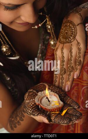 Sposa tenendo una lampada ad olio sul suo palm Foto Stock