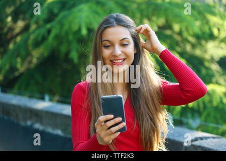 Sorpreso giovane donna utilizzando smart phone all'esterno. Eccitato ragazza urbano utilizzando il nuovo telefono mobile app nel parco della città.