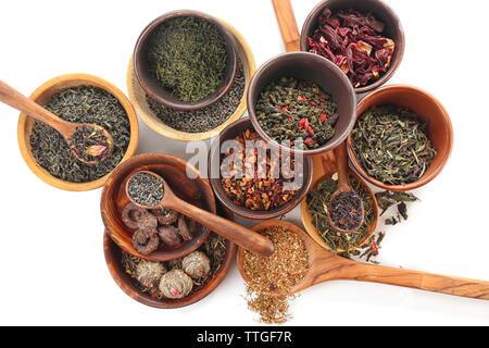 Varietà di tè a secco in pentole e cucchiai di legno isolato su bianco Foto Stock