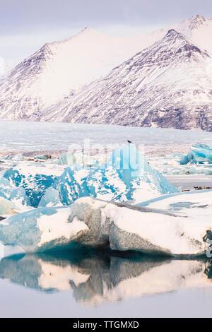 Visione idilliaca di iceberg nel lago contro le montagne dalle vette innevate durante il periodo invernale Foto Stock