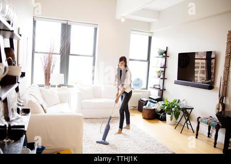La donna aspira il soggiorno a casa Foto Stock