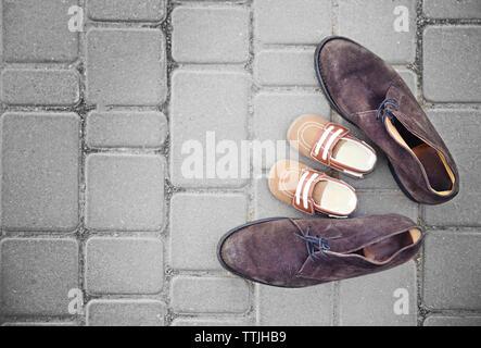 Padre le scarpe vicino alle scarpe da bambino sul marciapiede di sfondo Foto Stock
