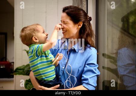 Giocoso figlio pizzicando la madre del naso tenendo il telefono cellulare a casa Foto Stock