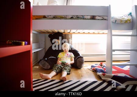 Per tutta la lunghezza del ragazzo in appoggio su Teddy bear sotto il letto di casa Foto Stock
