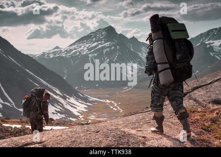 Gli escursionisti con zaini a piedi sulla montagna contro il cielo nuvoloso durante il periodo invernale Foto Stock