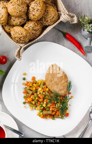 Angolo di alta vista di arrosto di carne con verdure servita nella piastra sulla tabella Foto Stock